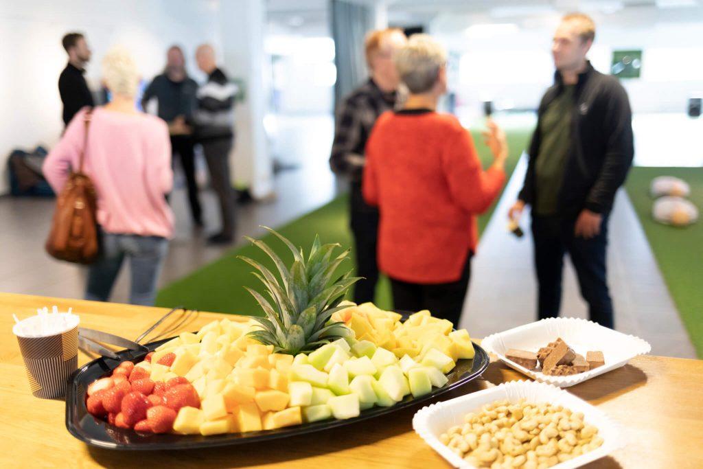 Frukt, choklad och nötter står framdukat. I bakgrunden syns ett tiotal personer som samtalar.