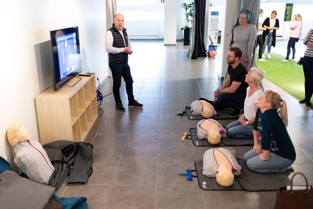 Tre personer är redo att testa att utföra kompressioner på utbildningsdockor från Laerdal.